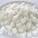 Diabetes concept - sugar cubes on white plat with fork and knife